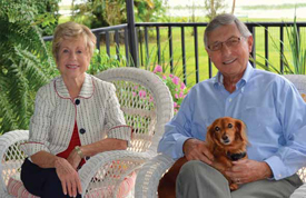 Nancy and George Hensley with their dog Katie on the porch at their Dinner Lake home.